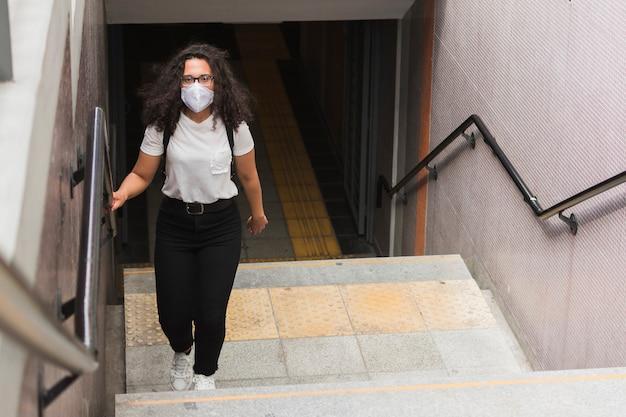 Junge frau, die eine medizinische maske trägt, während die treppe hinaufgeht