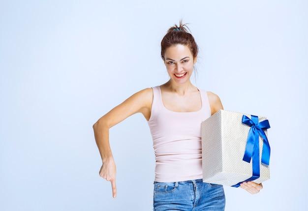 Junge frau, die eine mit blauem band umwickelte weiße geschenkbox hält und die person neben ihr einlädt, sie zu präsentieren