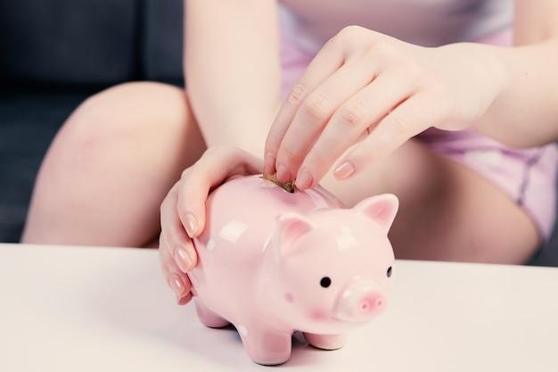 Junge frau, die eine münze in sparschwein als ersparnis für investition setzt