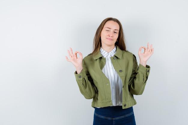 Junge frau, die eine ok geste zeigt, das auge im hemd, in der jacke zwinkert und selbstbewusst aussieht, vorderansicht.