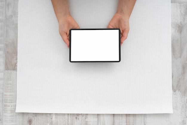 Junge frau, die eine online-yoga-klasse auf ihrem leeren tablett tut