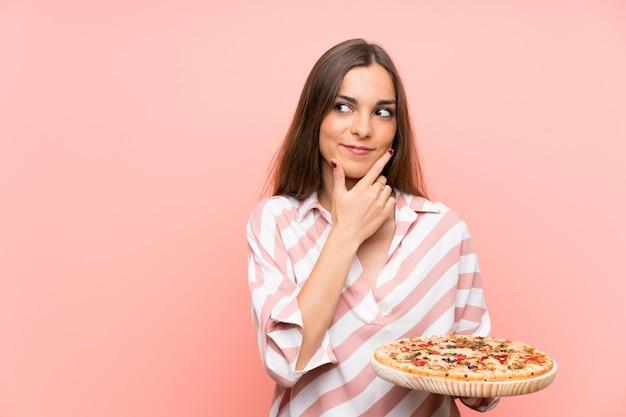 Junge frau, die eine pizza denkt eine idee hält