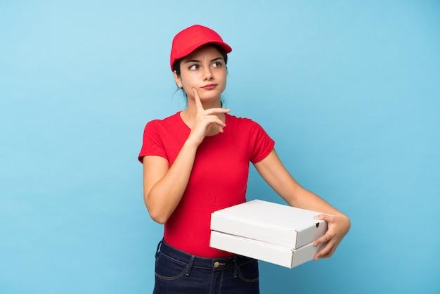 Junge frau, die eine pizza über der lokalisierten rosa wand denkt eine idee hält
