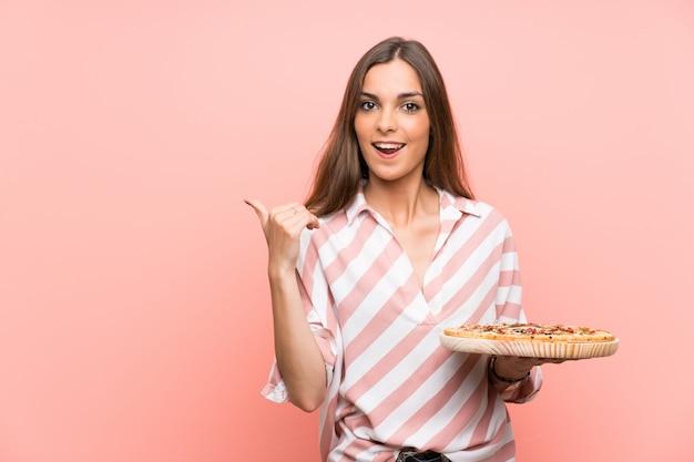 Junge frau, die eine pizza über der lokalisierten rosa wand zeigt auf die seite hält, um ein produkt darzustellen