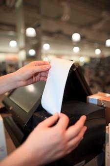 Junge frau, die eine rechnung / quittung für einen kunden am riesigen einkaufszentrum druckt