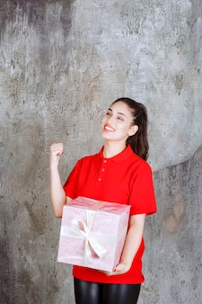Junge frau, die eine rosa geschenkbox hält, die mit weißem band eingewickelt wird und positives handzeichen zeigt.