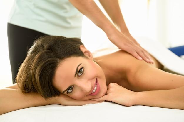 Junge frau, die eine rückenmassage in einer badekurortmitte empfängt.