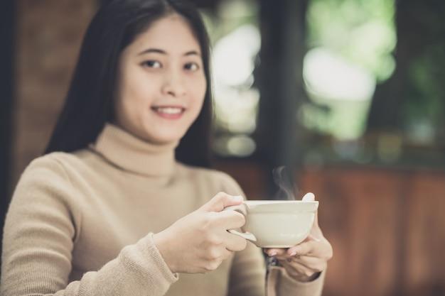Junge frau, die eine schale heißen kaffee in der naturansicht hält