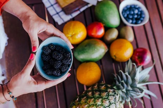 Junge frau, die eine schüssel brombeeren hält. zubereitung eines gesunden rezepts aus verschiedenen früchten, wassermelonen, orangen und brombeeren. mit einem mixer. selbstgemacht, drinnen, gesunder lebensstil