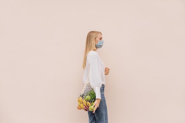 Junge frau, die eine schützende gesichtsmaske zur vorbeugung vor der coronavirus-covid-19-pandemie trägt, die eine einkaufstasche mit früchten hält. öko-lebensstil. bewusster konsum. neue normalität. platz kopieren