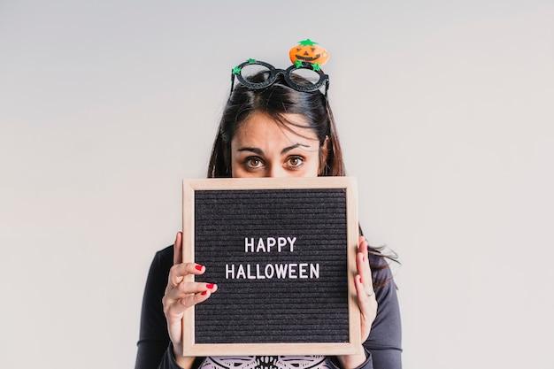 Junge frau, die eine schwarze weinlesebriefkarte mit glücklichem halloween-zeichen hält. lifestyle drinnen. skelettkostüm