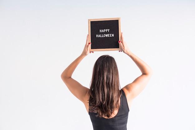 Junge frau, die eine schwarze weinlesetafel mit glücklichem halloween-zeichen hält. lifestyle drinnen