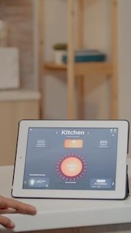 Junge frau, die eine smart-home-anwendung mit sprachbefehl verwendet, um das licht per tablet einzuschalten. dame, die die lichtsteuerungs-app in einem modernen haus mit einem automatisierungssystem verwendet, das die energieeffizienz steuert