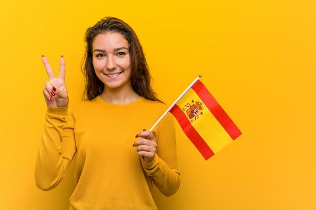 Junge frau, die eine spanische flagge hält, die nummer zwei mit den fingern zeigt