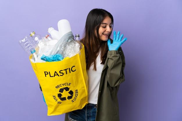 Junge frau, die eine tasche voll von plastikflaschen hält, um isoliert auf lila schreien mit weit offenem mund zur seite zu recyceln