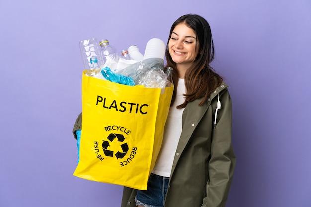 Junge frau, die eine tasche voll von plastikflaschen hält, um lokalisiert auf lila schauender seite zu recyceln