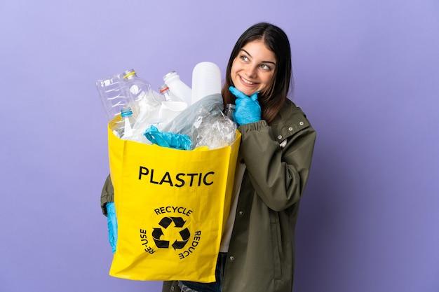 Junge frau, die eine tasche voll von plastikflaschen hält, um lokalisiert auf lila zu recyceln, während sie lächeln