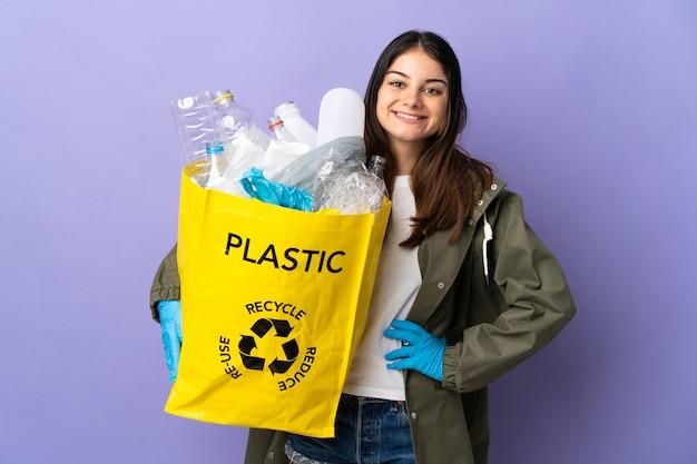 Junge frau, die eine tasche voll von plastikflaschen hält, um lokalisiert auf purpurne aufstellung mit armen an der hüfte und lächelnd zu recyceln