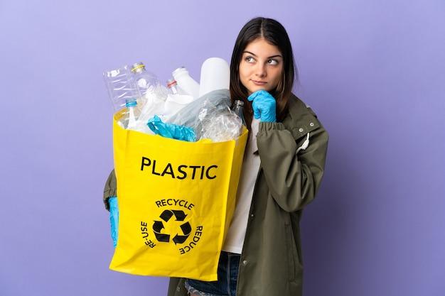 Junge frau, die eine tasche voller plastikflaschen hält, um isoliert auf purpur zu recyceln, das zweifel und denken hat