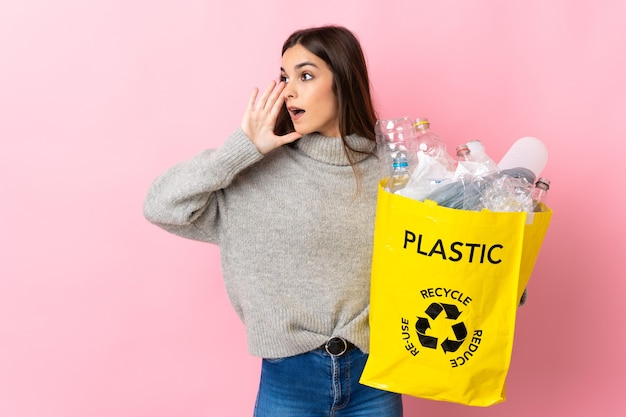 Junge frau, die eine tasche voller plastikflaschen hält, um isoliert auf rosa wand zu recyceln, die mit dem mund weit offen zur seite schreit