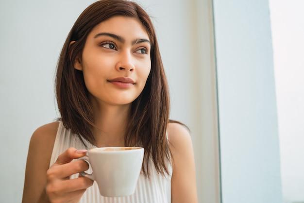Junge frau, die eine tasse kaffee am kaffeehaus trinkt.