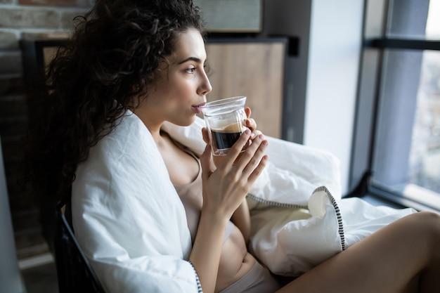 Junge frau, die eine tasse kaffee genießt, die an einem sonnigen morgen durch ein fenster sitzt