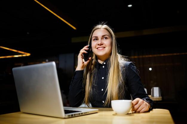 Junge frau, die eine tasse kaffee hält und laptop-computer verwendet, die am telefon spricht. geschäftsfrau, die von zu hause aus arbeitet. von zuhause aus arbeiten