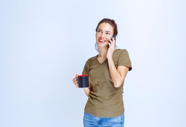 Junge frau, die eine tasse kaffee hält und mit dem telefon spricht