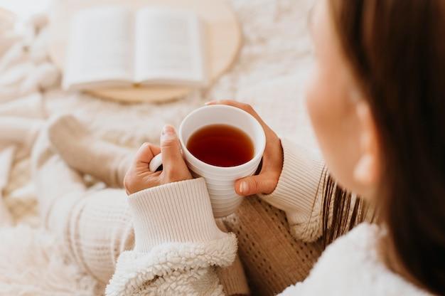Junge frau, die eine tasse tee hält, während die winterferien genießt