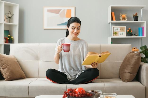 Junge frau, die eine tasse tee liest, ein buch in der hand hält und auf dem sofa hinter dem couchtisch im wohnzimmer sitzt?