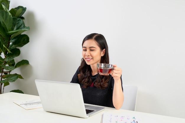 Junge frau, die eine teepause macht, während sie an einem tisch sitzt und an einem laptop arbeitet,
