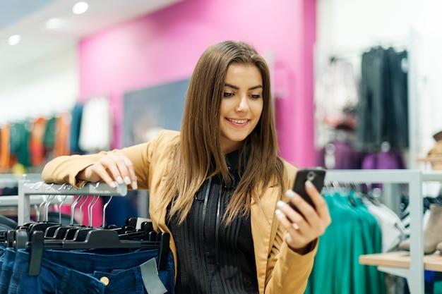 Junge frau, die eine textnachricht im einkaufszentrum liest