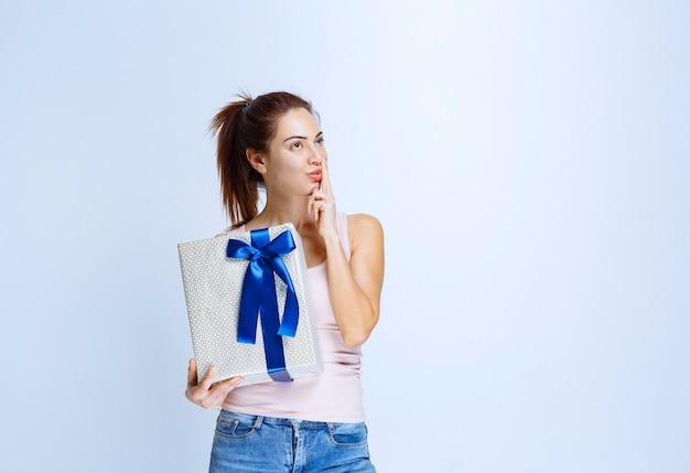 Junge frau, die eine weiße geschenkbox hält, die mit blauem band umwickelt ist und denkt und zögert