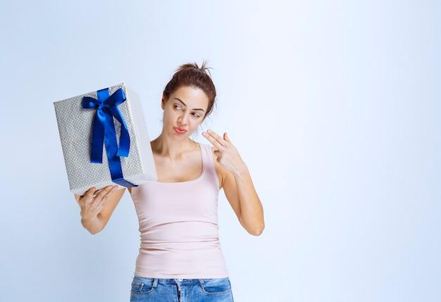 Junge frau, die eine weiße geschenkbox hält, die mit blauem band umwickelt ist und es demonstriert