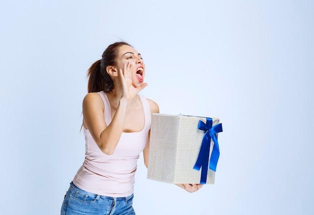 Junge frau, die eine weiße geschenkbox hält, die mit blauem band umwickelt ist und schreit, um aufmerksamkeit zu erregen