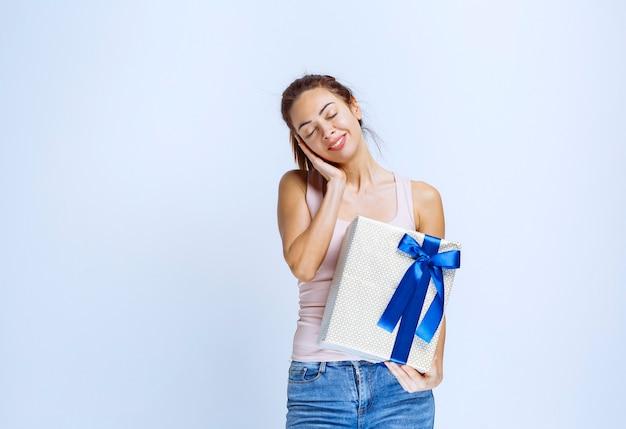 Junge frau, die eine weiße geschenkbox hält, die mit blauem band umwickelt ist, und sieht müde und erschöpft aus