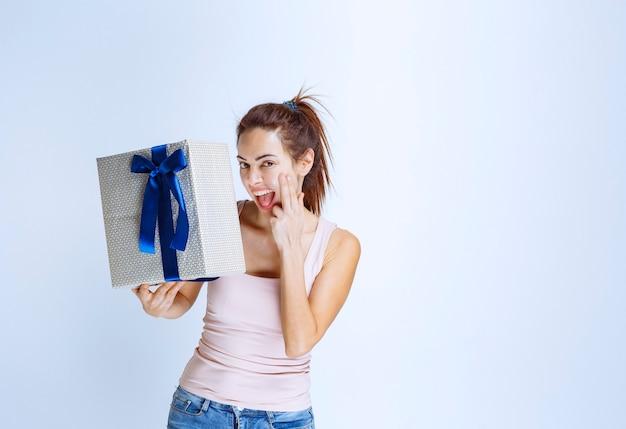 Junge frau, die eine weiße geschenkbox hält, die mit blauem band umwickelt ist