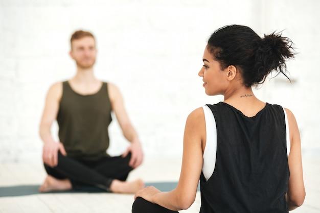 Junge frau, die eine yoga-klasse mit männlichem ausbilder hat