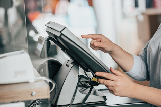 Junge frau, die eine zahlung für ein paar kleidungsstücke durch touchscreen-schatzkammer in einem riesigen einkaufszentrum auflädt?