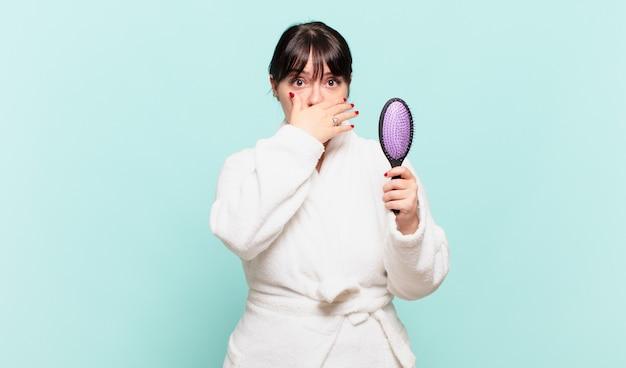 Junge frau, die einen bademantel trägt, der den mund mit den händen mit einem schockierten, überraschten ausdruck bedeckt, ein geheimnis hält oder oops sagt