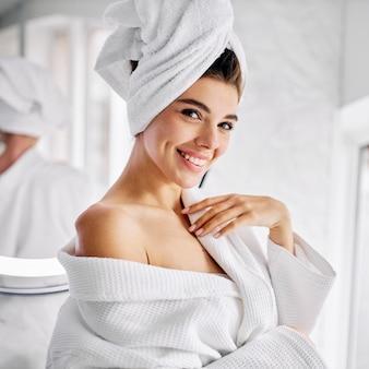 Junge frau, die einen bademantel und ein handtuch auf ihren haaren trägt