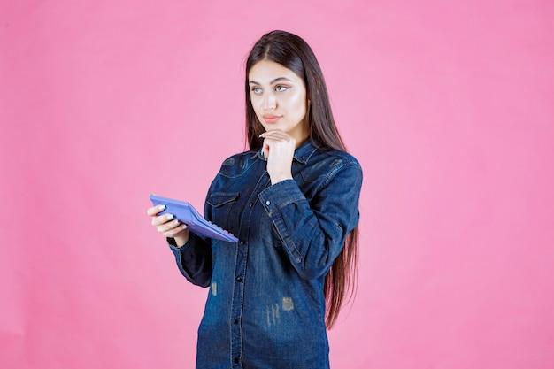 Junge frau, die einen blauen taschenrechner hält und denkt