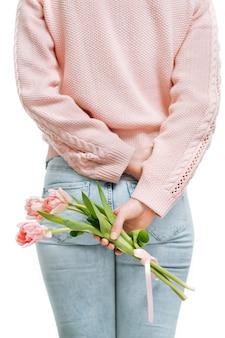 Junge frau, die einen blumenstrauß der rosa tulpen hinter ihrem rücken auf einem weißen hintergrund hält. textraum, selektiver fokus.