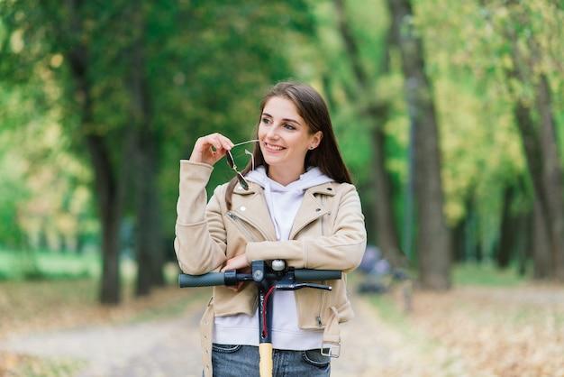 Junge frau, die einen elektroroller in einem herbstpark reitet. grüner transport, stauprobleme.