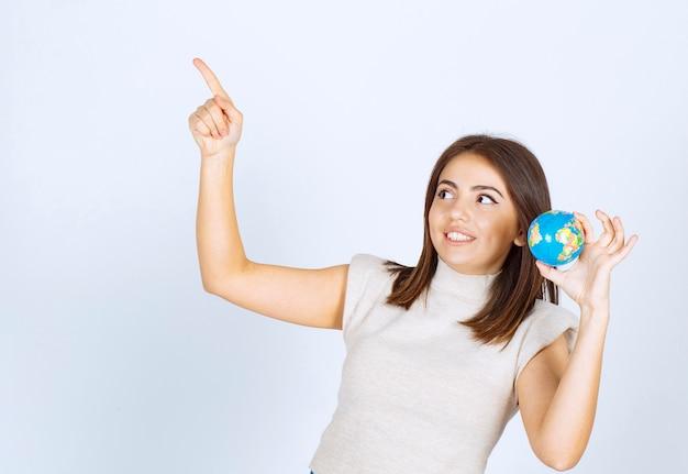 Junge frau, die einen erdkugelball hält und mit einem zeigefinger nach oben zeigt