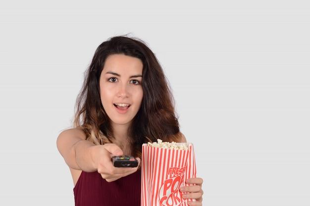 Junge frau, die einen film aufpasst und popcorn isst.