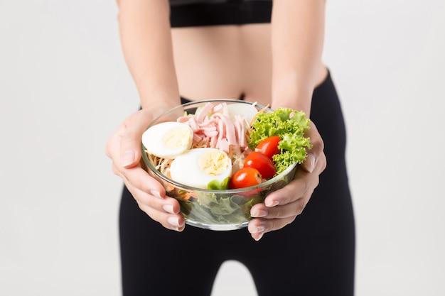 Junge frau, die einen gesunden obstsalat nach training isst. fitness und gesunder lebensstil.