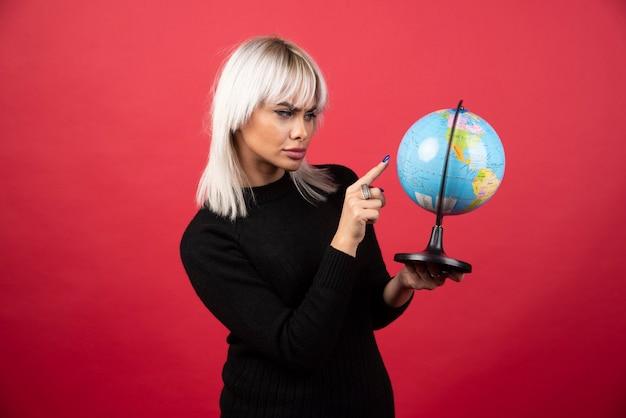 Junge frau, die einen globus auf einem roten hintergrund zeigt. hochwertiges foto