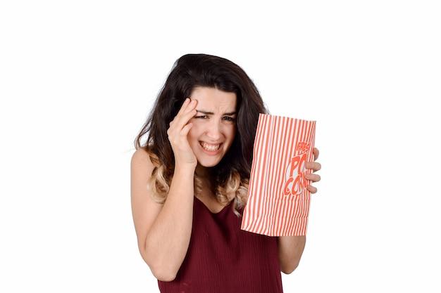 Junge frau, die einen gruseligen film aufpasst und popcorn isst.