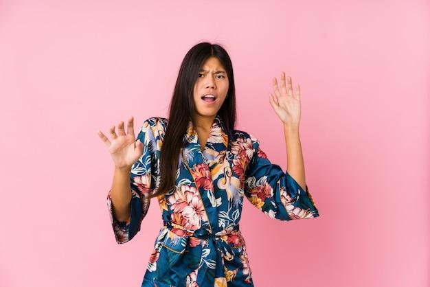 Junge frau, die einen kimono-pyjama trägt, der wegen einer drohenden gefahr schockiert wird